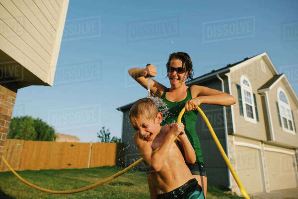 Playful mother pouring water on son using hose pipe in yard Royalty-free stock photo