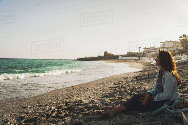 Thoughtful woman sitting on beach while looking at view Royalty-free stock photo