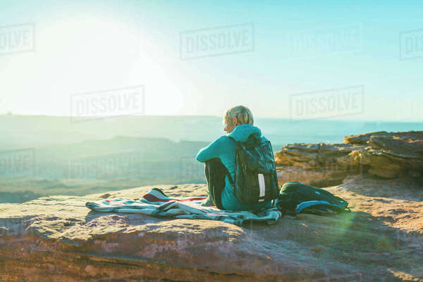 Rear view of female hiker sitting on mountain against sky during sunny day Royalty-free stock photo
