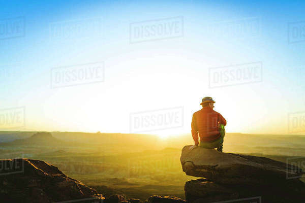 Rear view of male hiker sitting on cliff against sky during sunset at Canyonlands National Park Royalty-free stock photo