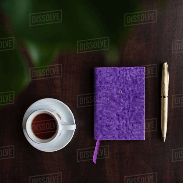 Overhead view of coffee in cup and diary on table Royalty-free stock photo