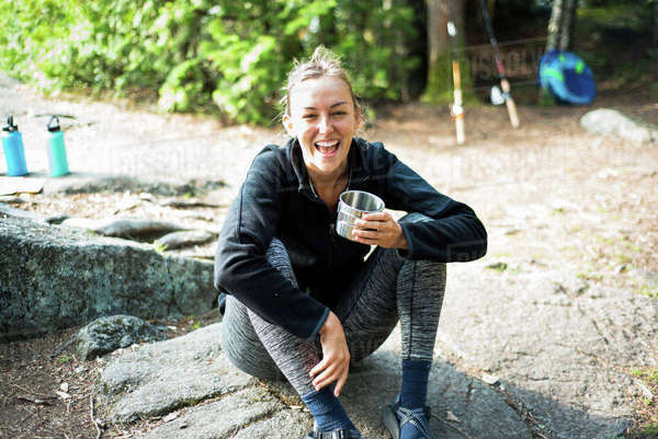 Cheerful woman having coffee while sitting at campsite Royalty-free stock photo