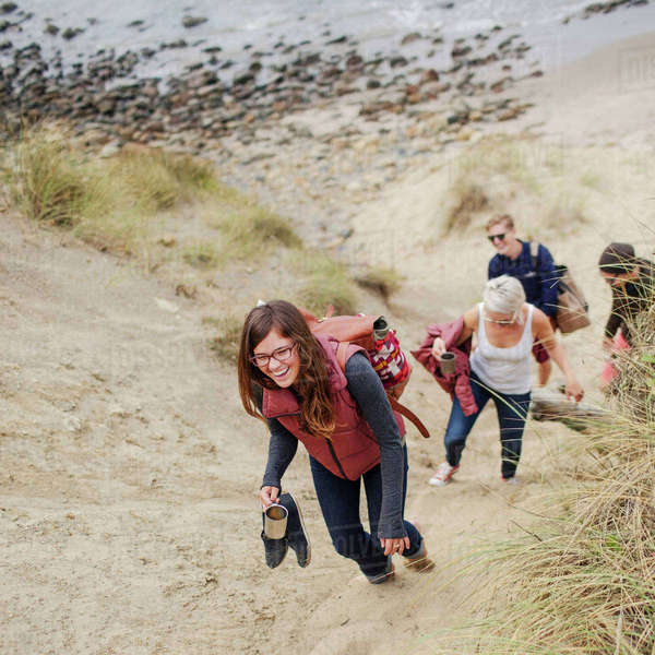 Happy woman walking with friends on sand at beach Royalty-free stock photo