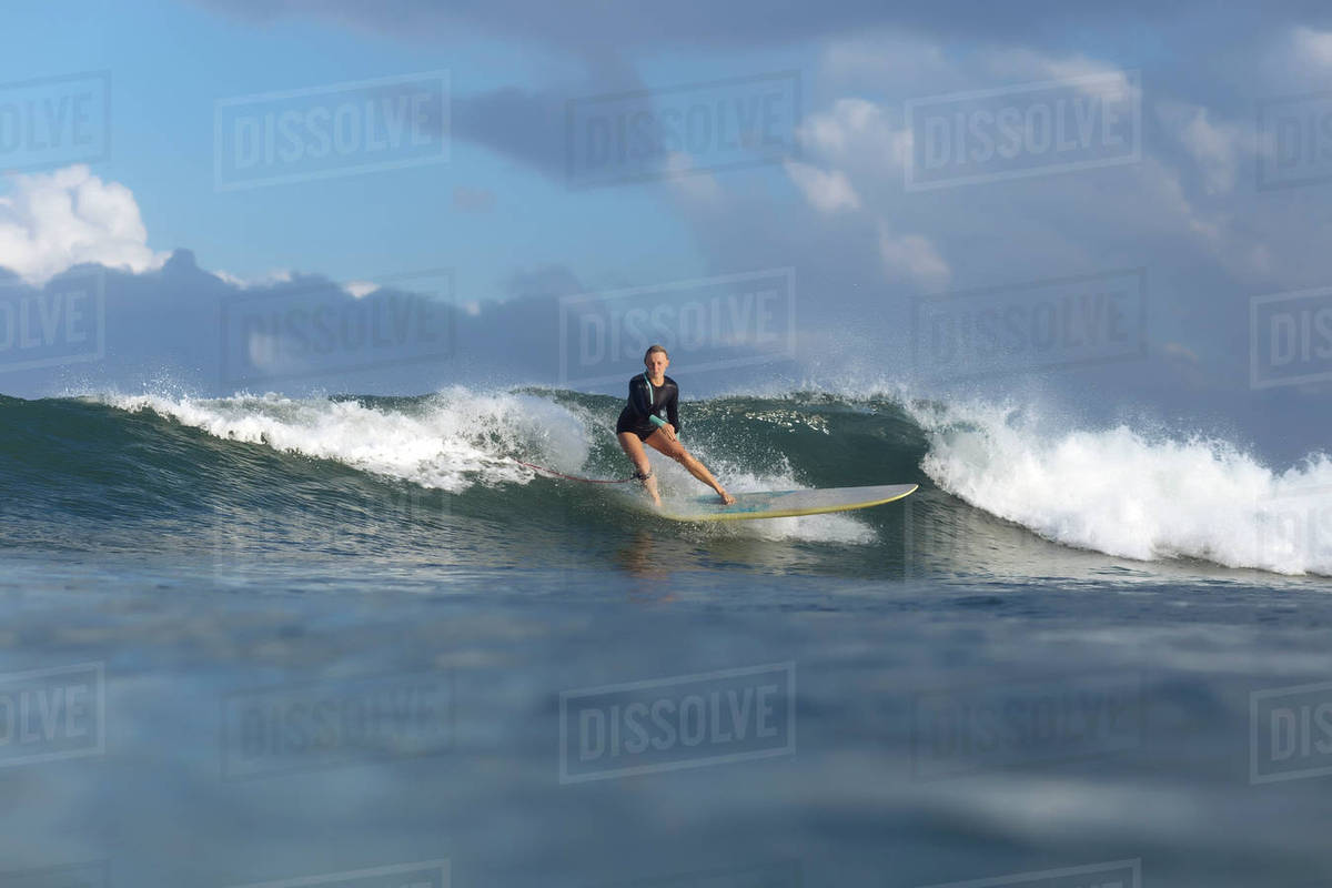 Carefree Woman Surfing On Sea Against Cloudy Sky Stock Photo