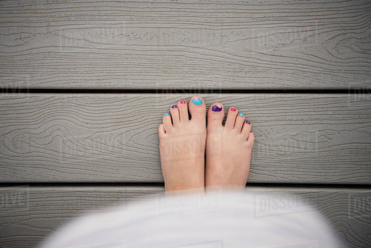 Low Section Of With Colorful Nail Polish Standing On Boardwalk
