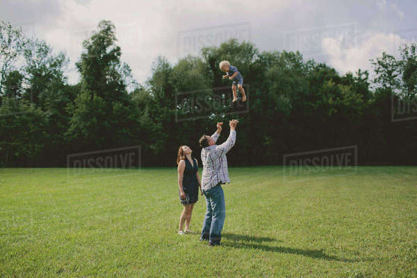 Woman looking at man throwing son in air Royalty-free stock photo