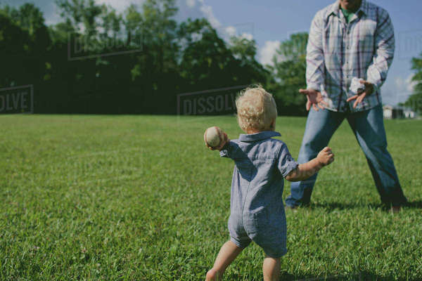 Father and son playing with ball on grassy field Royalty-free stock photo