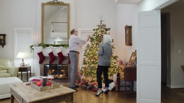 Medium wide shot of a senior couple decorating a Christmas tree Royalty-free stock video