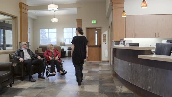 Steadicam shot of a nurse pushing a senior woman in a wheelchair Royalty-free stock video