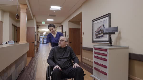 Steadicam shot of a nurse pushing a senior man in a wheelchair Royalty-free stock video