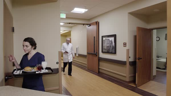 Medium shot of nurse taking food into a room Royalty-free stock video