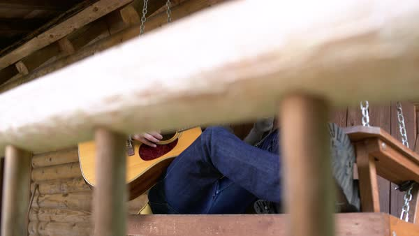 Man playing guitar while sitting on a porch swing outdoors Royalty-free stock video