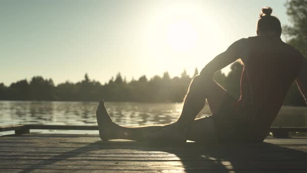 A young man doing yoga on a pier at sunrise Royalty-free stock video