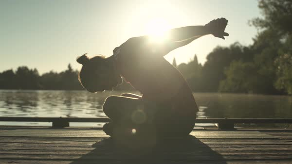 A young man doing yoga on a dock at sunrise Royalty-free stock video