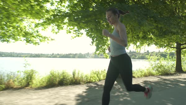 A young woman running by a lake Royalty-free stock video