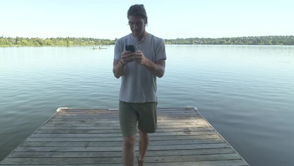 A young man using a smartphone on a pier Royalty-free stock video