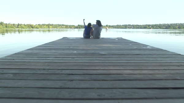 A young couple sitting on a pier Royalty-free stock video
