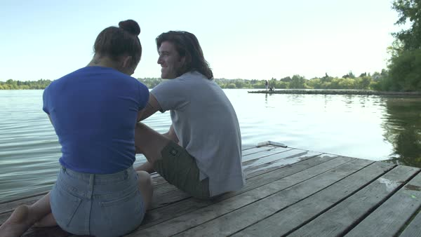 A young man and a young woman talking on a dock Royalty-free stock video