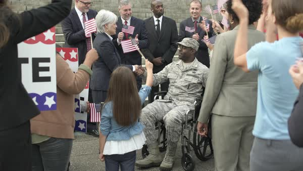 A politician greeting a soldier sitting in a wheelchair Royalty-free stock video