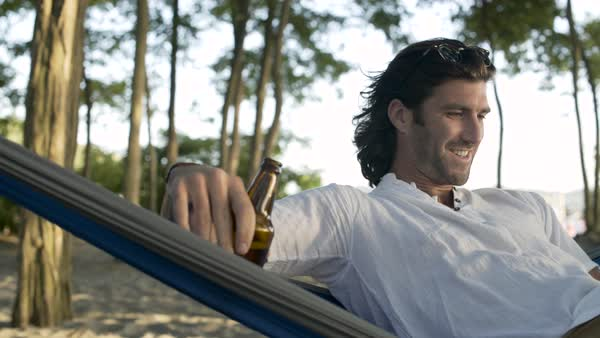A man drinking beer in a hammock Royalty-free stock video