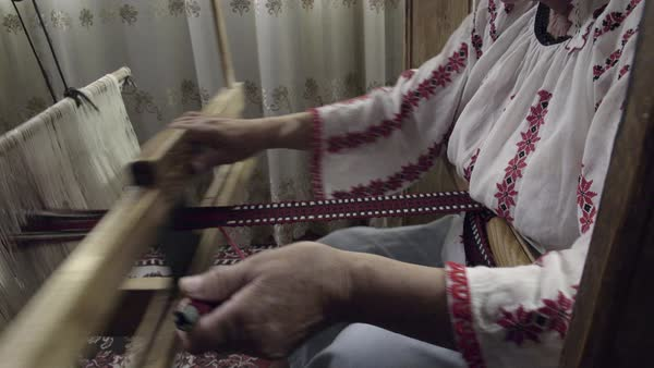 A dolly out shot of weaver who is weaving a traditional belt on a obsolete wooden weaving machine. Royalty-free stock video