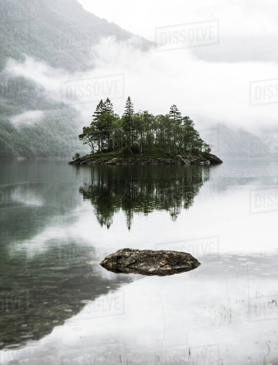 View of tree covered island in lake with lushy mountain in background, Norway Royalty-free stock photo