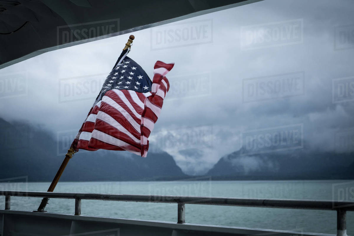 American flag on boat against cloudy sky, Alaska, United States of America Royalty-free stock photo