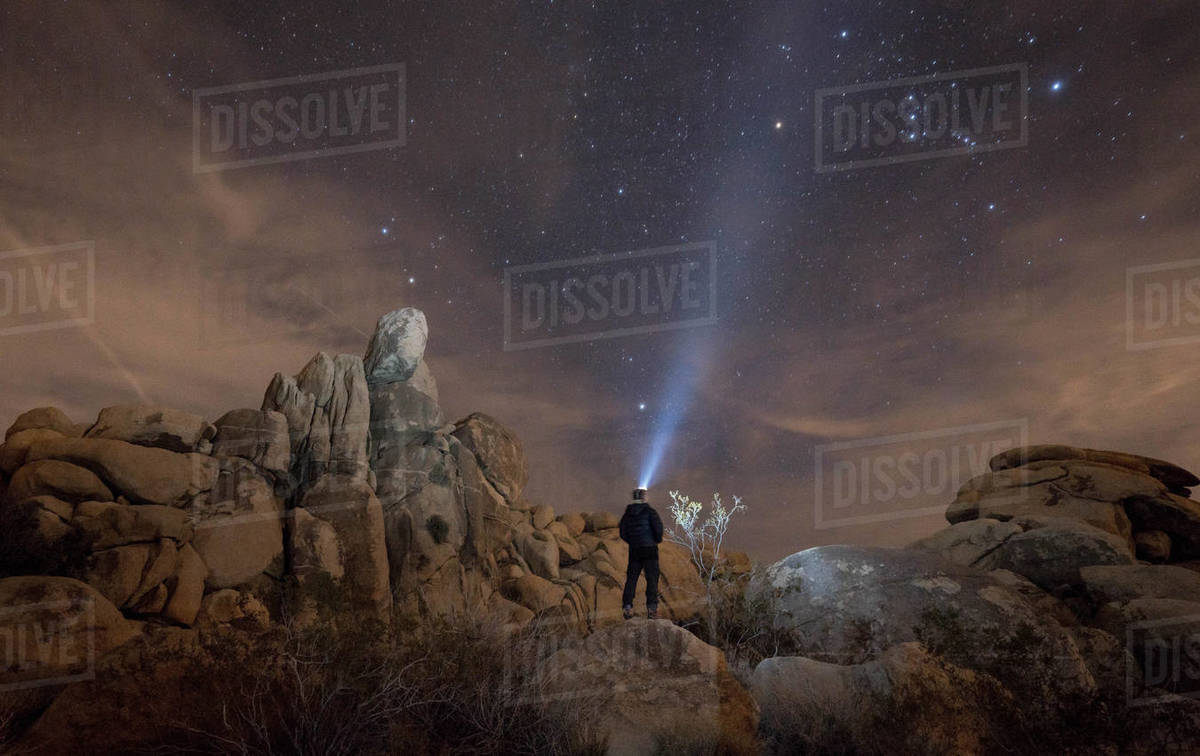 Rear view of a woman with headlamp looking at starry sky while standing on rock Royalty-free stock photo