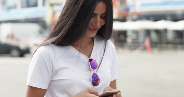 Cute young woman with long brown hair looking at her mobile device while texting or browsing the internet Royalty-free stock video