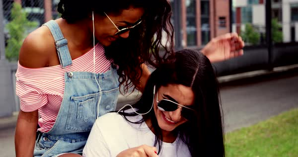 Two laughing young women listening to music together sharing a set of earplugs as they listen to tunes on a mobile phone outdoors in an urban park Royalty-free stock video
