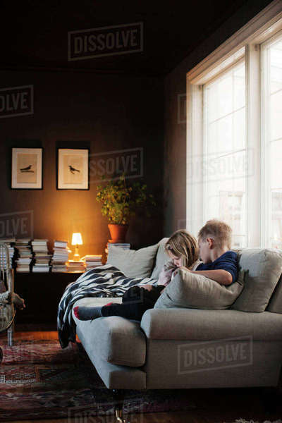 Denmark, Boy (8-9) and girl (4-5) sitting on sofa in living room Royalty-free stock photo