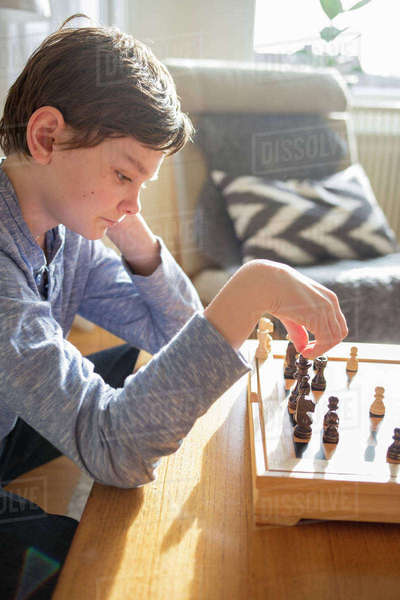 Sweden, Boy (12-13) playing chess in living room Royalty-free stock photo