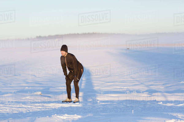 Sweden, Vasterbotten, Roback, Jogger resting in snowy field Royalty-free stock photo