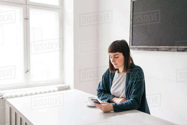 Sweden, Young woman using mobile phone at desk in office Royalty-free stock photo