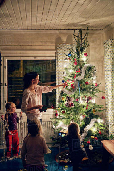 Finland, Mother with daughters (12-17 months, 2-3, 4-5) decorating christmas tree Royalty-free stock photo
