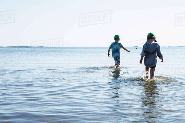 Finland, Helsinki, Drumso, Boys walking in water Royalty-free stock photo