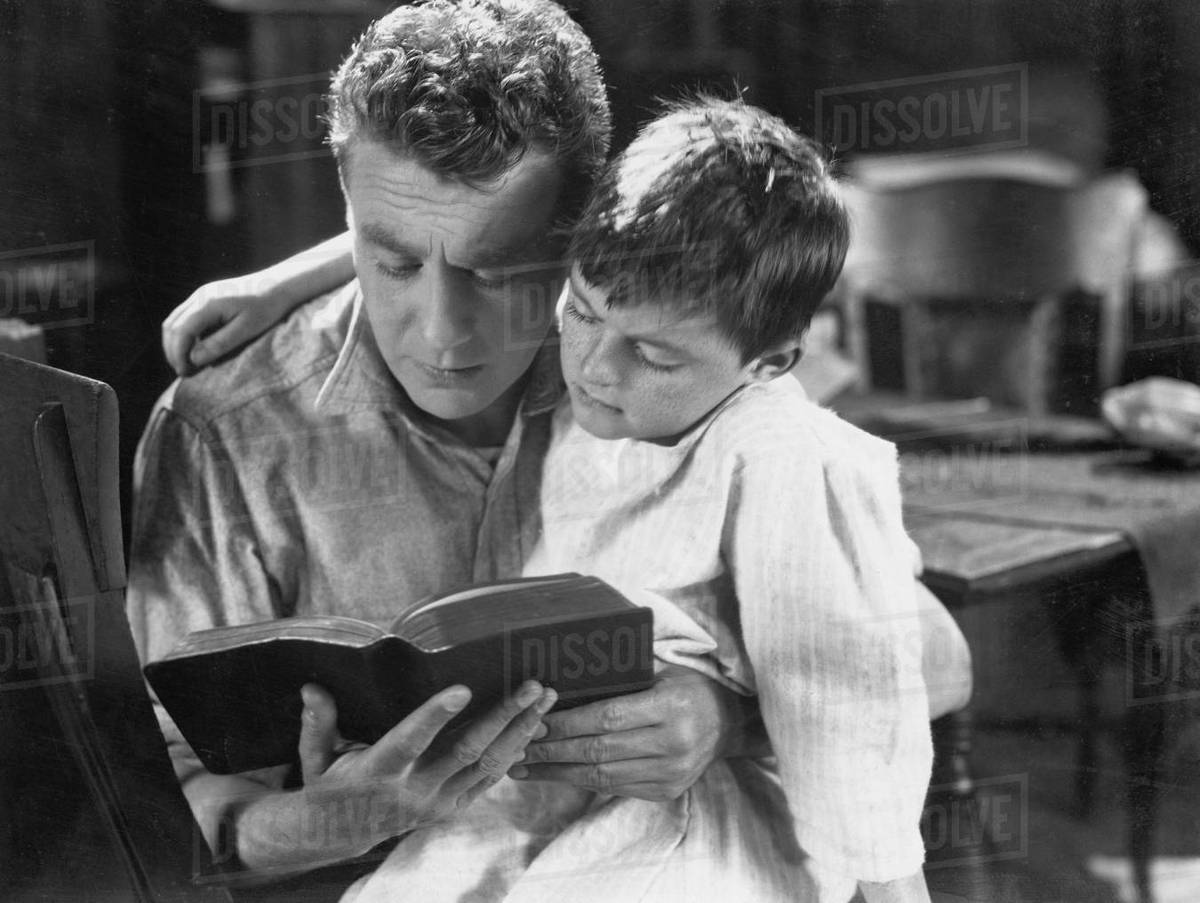 Portrait of dad reading bedtime story to son