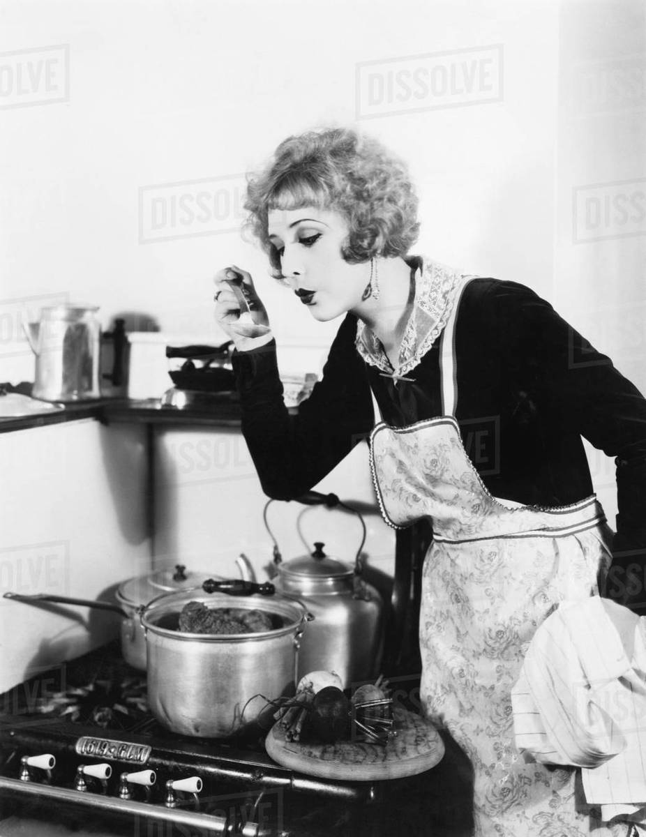 Young woman in an apron in her kitchen tasting her food from a pot ...