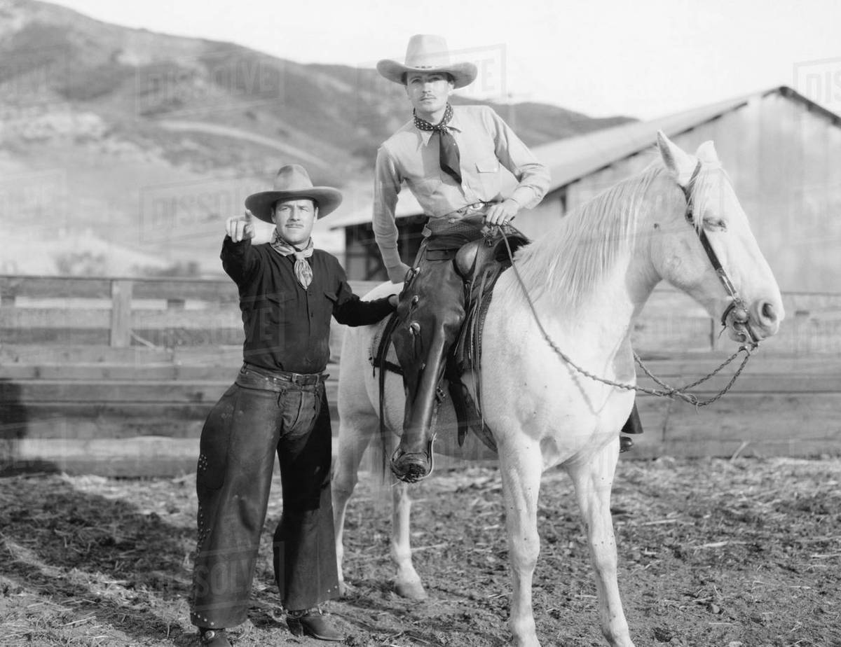 Two Cowboys And A White Horse Stock Photo Dissolve