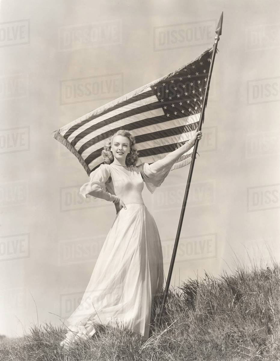 Proud woman in gown holding American flag on hill - Stock Photo ...