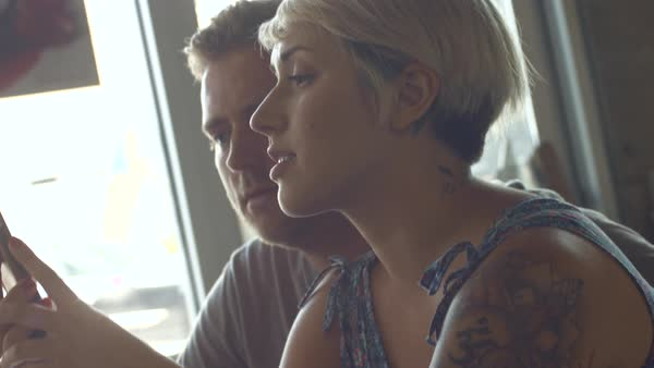 Hand-held shot of a man and a woman using a smartphone Royalty-free stock video