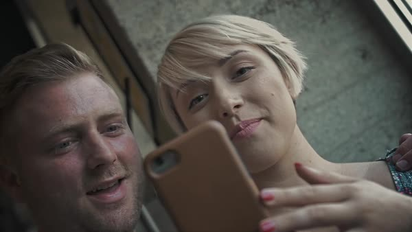 Slow motion shot of a couple looking at a cell phone and laughing Royalty-free stock video