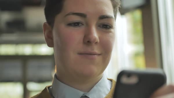 Dolly shot of a genderqueer person using a smartphone in a cafe Royalty-free stock video