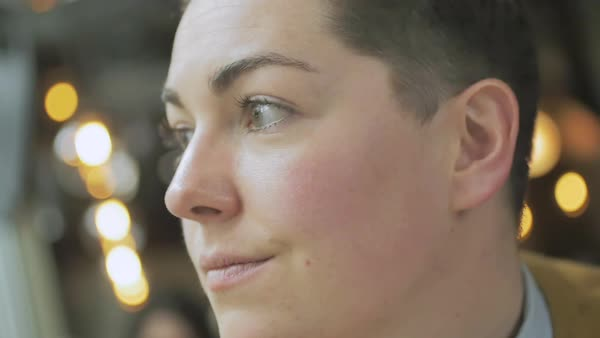 Hand-held shot of a genderqueer person sitting in a cafe and looking away Royalty-free stock video