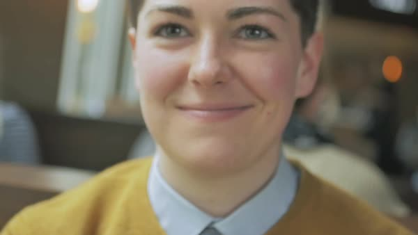 Slow motion shot of a smiling genderqueer person raising hand to mouth Royalty-free stock video