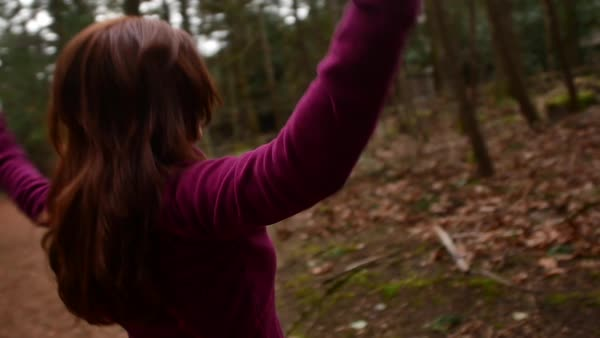Arc shot of a woman doing jumping jacks in a forest Royalty-free stock video