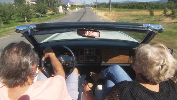 Locked-off shot of a couple traveling by a convertible car on a rural road Royalty-free stock video