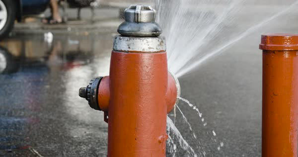 AN establishing shot of a busted Fire Hydrant spitting water onto a New York City street Royalty-free stock video