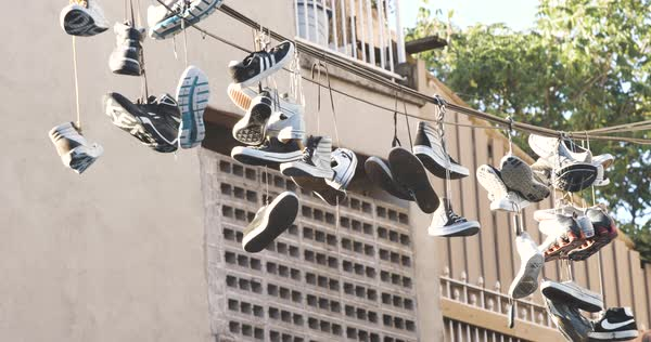 An establishing shot of Sneakers hanging over a telephone line in Brooklyn, NYC Royalty-free stock video