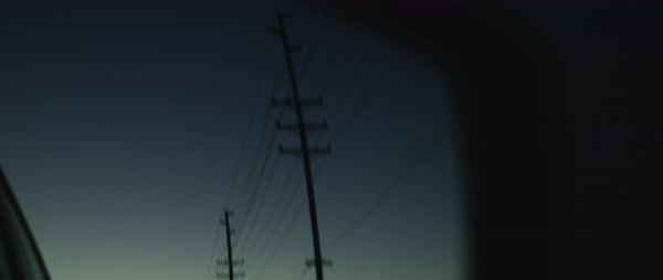 Hand-held shot of driving past utility poles seen in side view mirror Royalty-free stock video